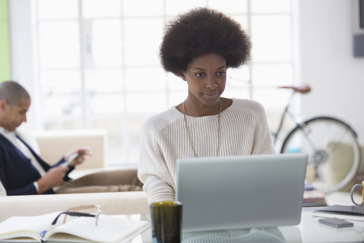 Young woman with afro working from home at laptop
